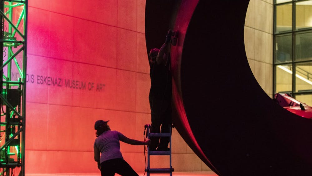 Giorgio Gikas, 63, buffs the Indiana Arc while 30-year-old Terra Gillis held his ladder July 13 in front of the Eskenazi Museum of Art. The museum will celebrate its highly anticipated grand reopening Nov. 7.