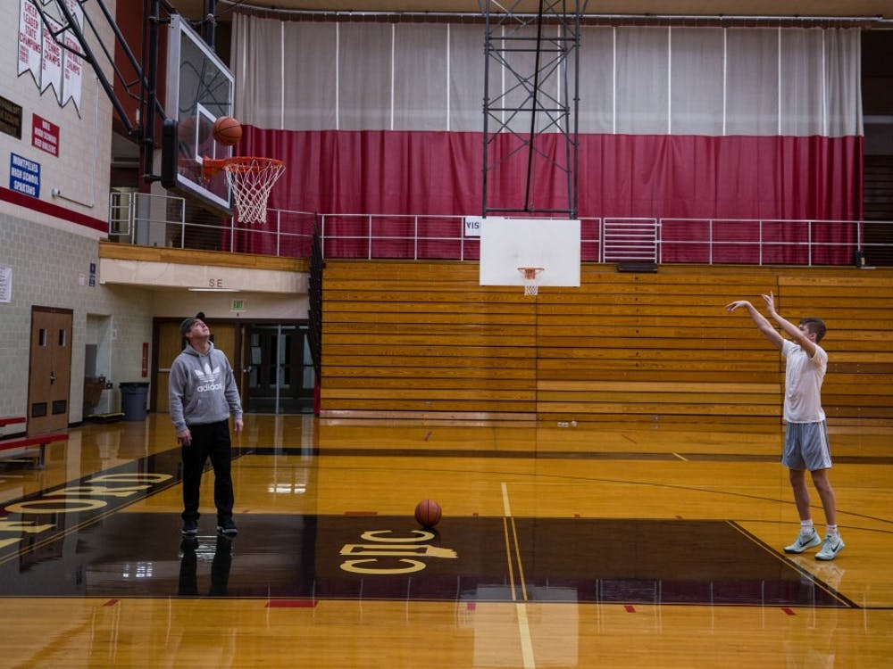 Ted Brown, left, rebounds free throws for his son, Luke Brown, at an early morning practice at Blackford High School in Hartford City, Indiana. Luke, originally from Brownsburg, Indiana, came to Blackford because of the head coach, Jerry Hoover.