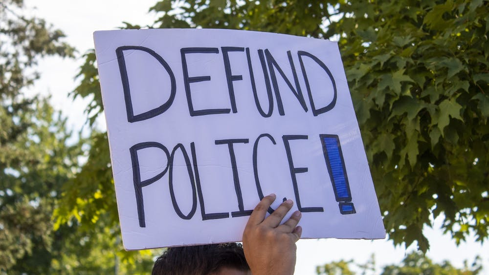 "A protester holds a sign reading ""Defund Police"" on Aug. 18 outside City Hall."