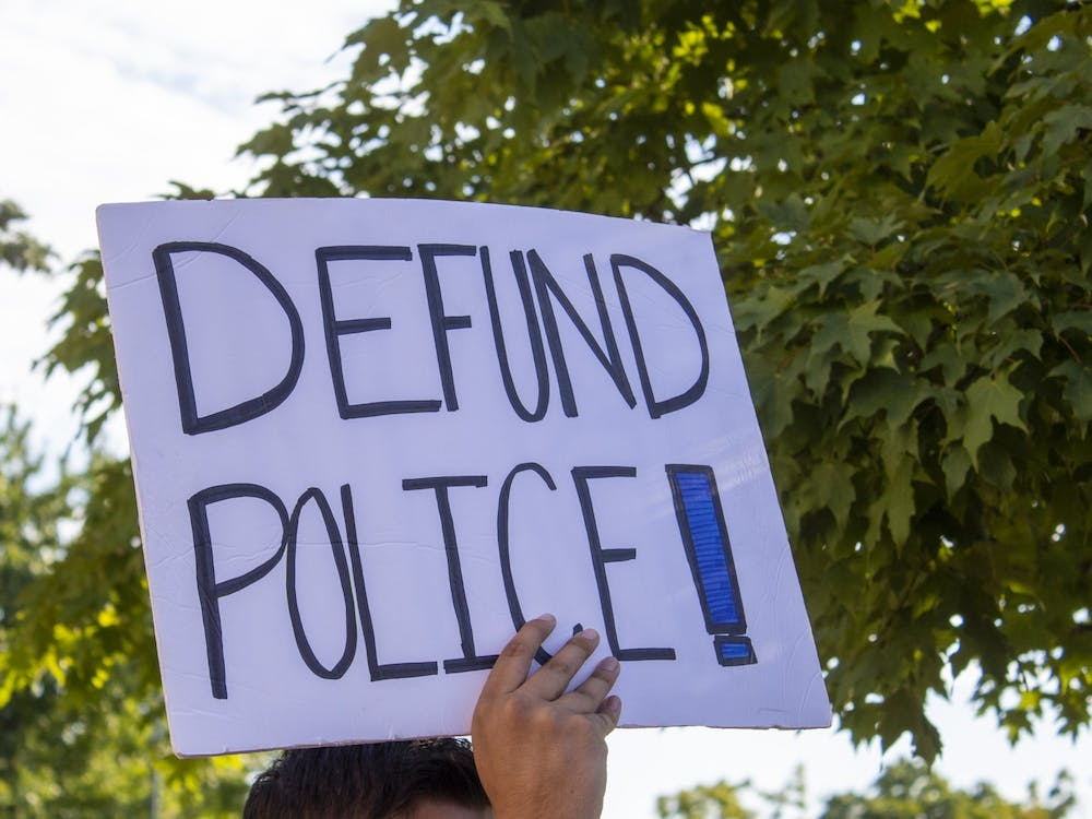"""A protester holds a sign reading """"Defund Police"""" on Aug. 18 outside City Hall."""