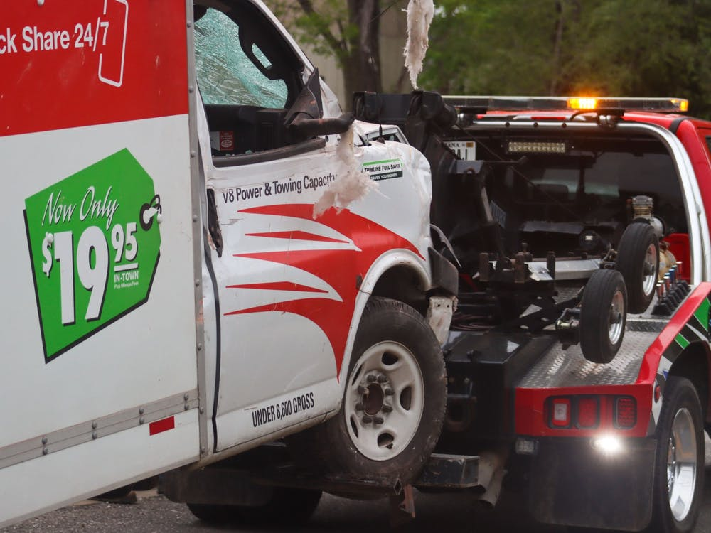 The U-Haul truck that crashed into Evil by the Needle is towed from the scene Sunday night. Two people were in the building at the time of the crash and are receiving medical attention for injuries, according to the owner of Evil by the Needle's daughter Kian Rio.