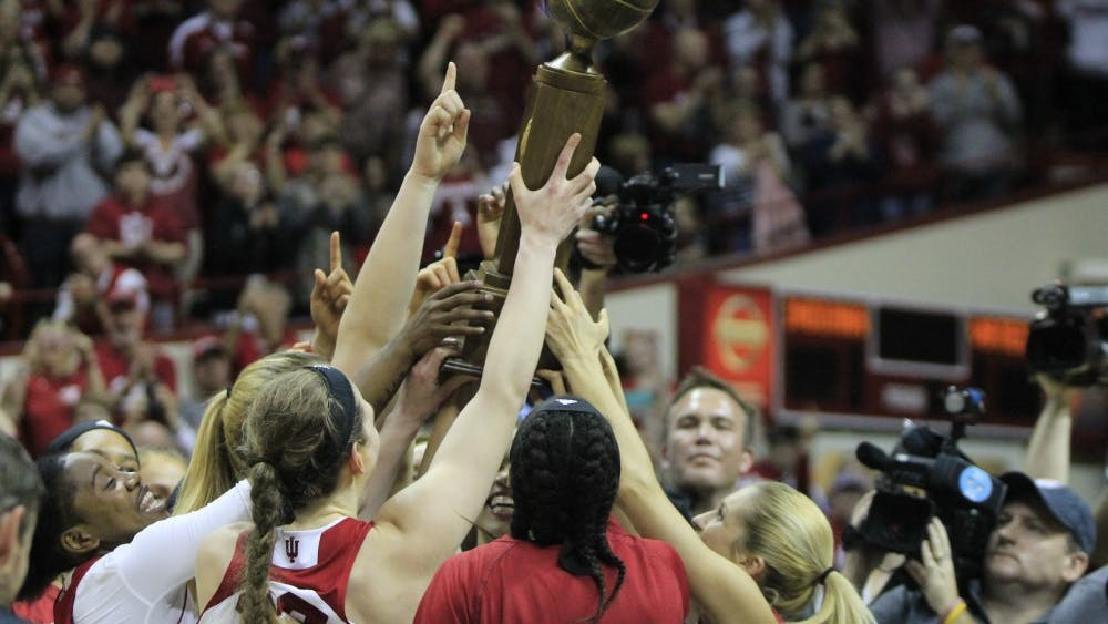 The IU women's basketball team huddles March 31, 2018, with the WNIT trophy after defeating Virginia Polytechnic Institute and State University. The 2018 women's basketball season ended with a win March 31.