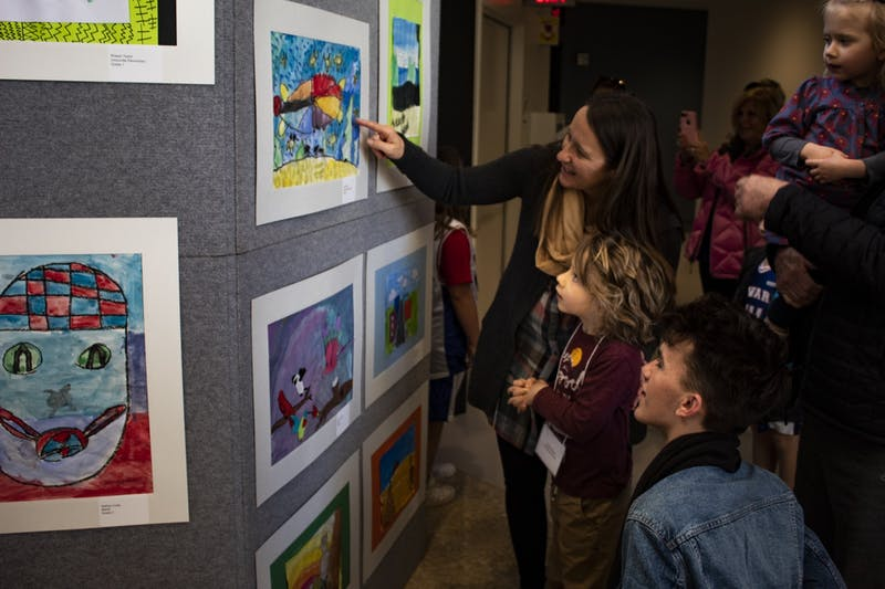 Mother Sara Elgi points to kindergartener Julian Parks' artwork March 7 in the Sidney and Lois Eskenazi Museum of Art. Student artwork was showcased on the second floor of the in celebration of Youth Art Month.museum .