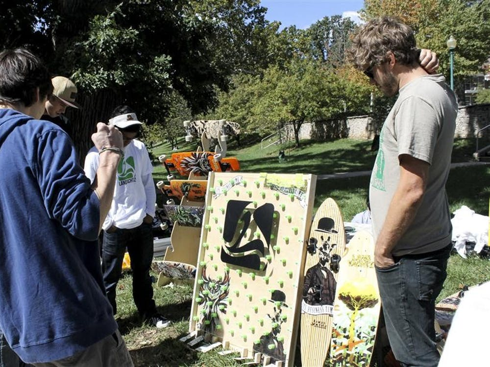 Freshman Adam Ketzenberger, left, reacts after winning a longboard deck, during a promotion for Landyachtz Longboards on Tuesday in Dunn Meadow. Bloomington was one of the company's stops during its promotional tour.
