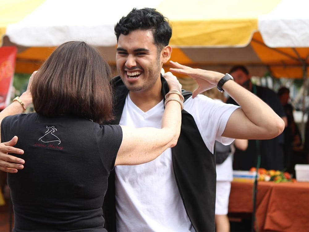 Gabriel Escobedo dances with Barbara Leininger, owner of the Arthur Murray Dance Studio, during a salsa dancing demonstration at the Bloomington Farmer's Market on Saturday.