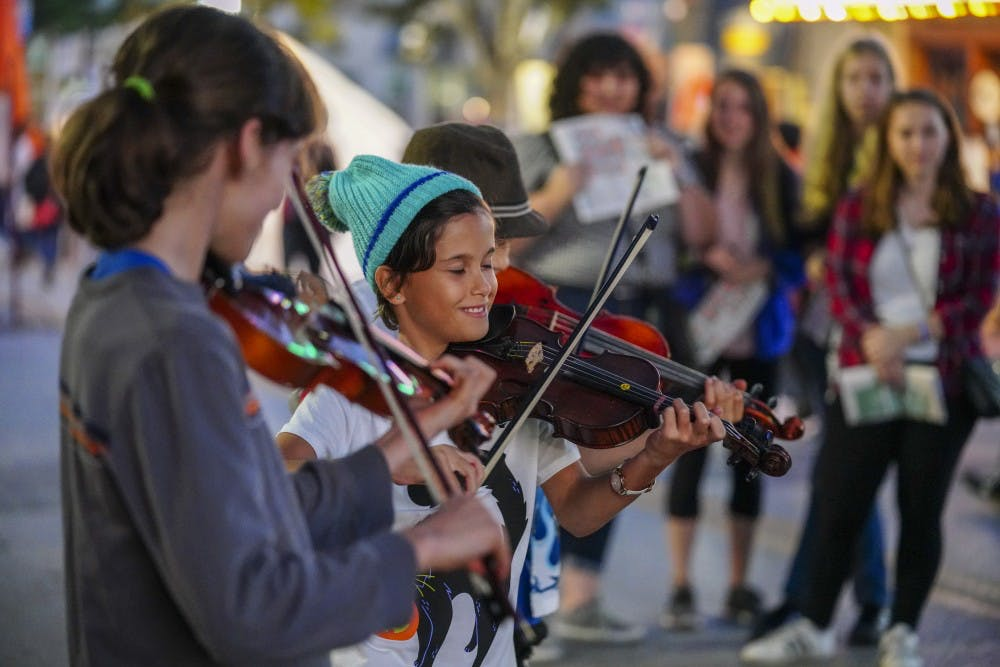 <p>Viking Kittens, an orchestral trio, gives a live street performance for attendees of the 2018 Lotus World Music and Arts Festival outside of the Buskirk-Chumley Theater on Sept. 28.</p>
