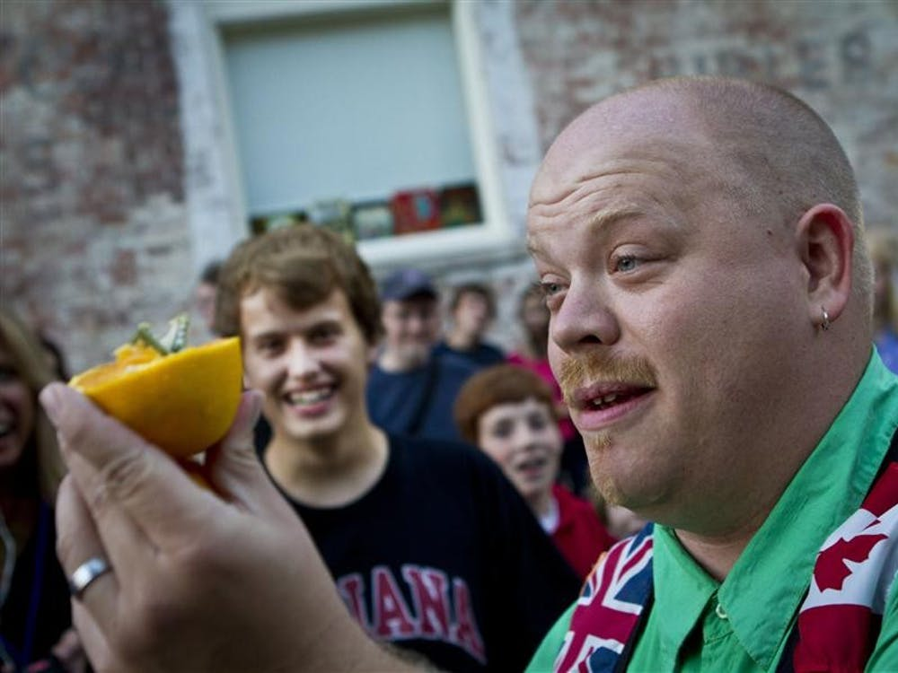Magician Andrew Baerlocker cuts a five dollar bill out of an orange during the 19th annual Lotus World Music & Arts Festival on Friday in downtown Bloomington.