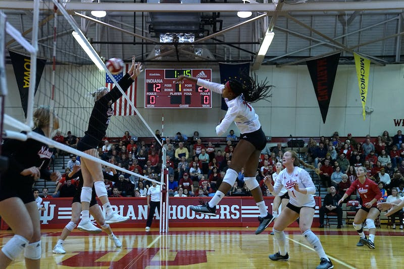 Then-junior middle blocker Deyshia Lofton spikes the ball for a kill against two University of Nebraska — Lincoln defenders on Nov. 17 in University Gym. IU's nonconference schedule will begin this weekend at the Indiana Invitational, with four matches being played between Friday and Saturday at Wilkinson Hall.