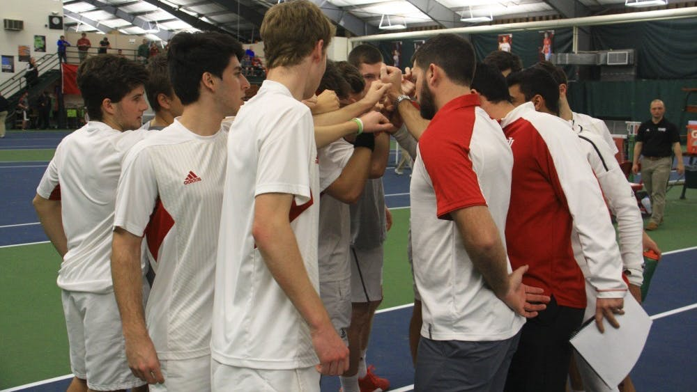 The IU men's tennis team gathers in a circle with coaches before a singles match against Purdue at the IU Tennis Center in April of 2017.