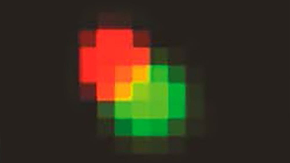 A zoomed-in view of the particle used in a study to show rotational movement in nanoparticles is seen here. Each probe consisted of a 200nm amine-modified green fluorescent particle with a 40nm carboxylate-modified red fluorescent particle attached to its surface.