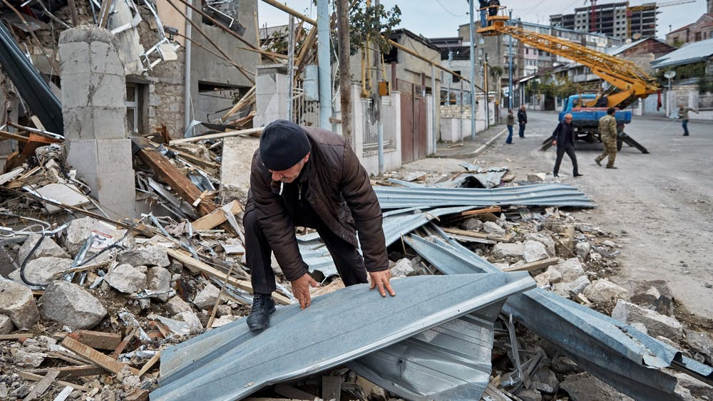 A man rummages through the remains of a home that was damaged by Azeri artillery Oct. 10 in Stepanakert, Azerbaijan. Residents of the Nagorno-Karabakh capital experienced relative calm in the city following a ceasefire agreement that was made between Azerbaijan and Armenia the previous night in Moscow.
