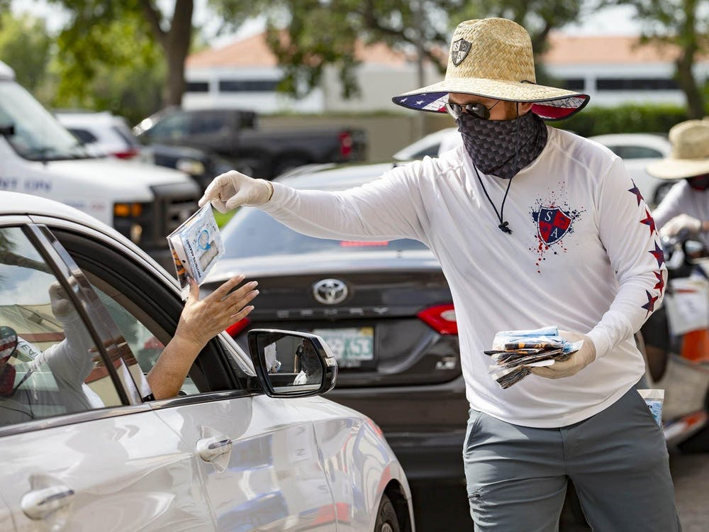 Alex Liberatore hands out free tubular bandanas to the public April 15 in Boca Raton, Florida.