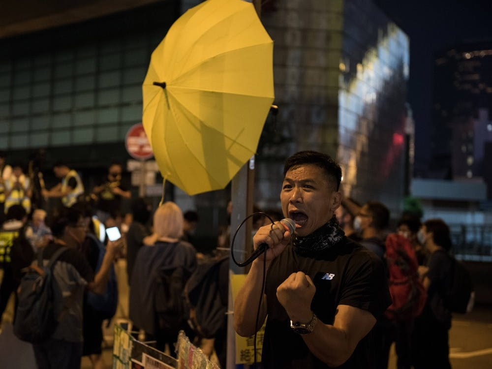 "A protester shouts various slogans during a demonstration in Hong Kong. Demonstrators gathered for an anti-authoritarian rally that marked the fifth anniversary of the beginning of the 2014 ""Umbrella Movement."" Thousands of protesters gathered peacefully, but minor clashes between protesters and police escalated through the night, leading to a police dispersal operation."