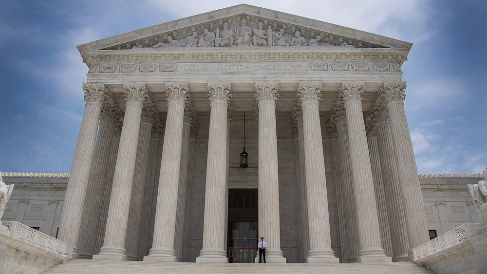 A police officer stands guard June 15, 2017, on the steps of the U.S. Supreme Court in Washington, D.C. The Supreme Court affirmed a ruling against the NCAA on Monday, declaring that the collegiate athletics organization violated antitrust laws.
