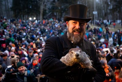 A member of the Punxsutawney Groundhog Club's Inner Circle holds Phil for a picture Feb. 2 after he makes his weather prediction on Groundhog Day.