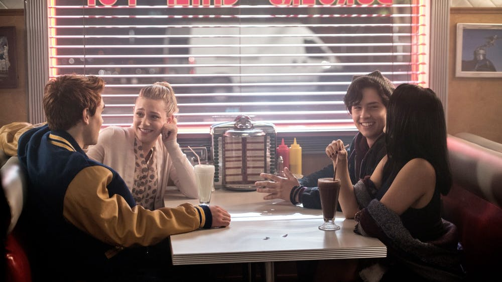 "Cole Sprouse, as Jughead Jones, K.J. Apa, as Archie Andrews, Lili Reinhart, as Elizabeth ""Betty"" Cooper, and Camila Mendes, as Veronica Lodge, appear on the set of ""Riverdale"" in 2017."