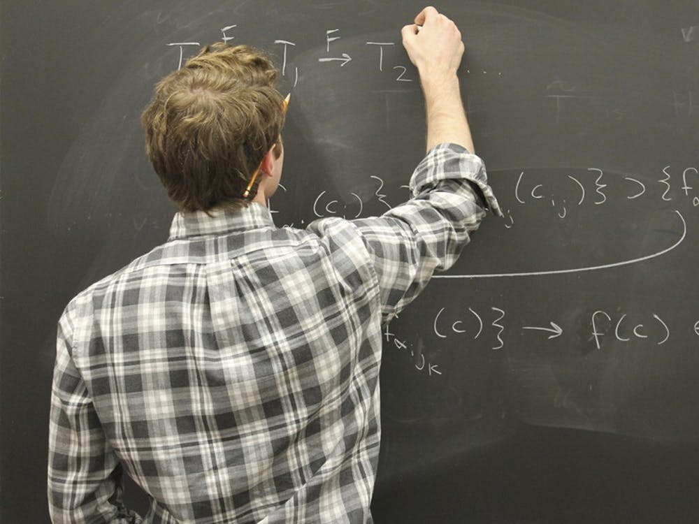 Grant Schumacher, an undergraduate majoring in math and physics, explains a complicated math concept using equations during a meeting with his research group on Wednesday.