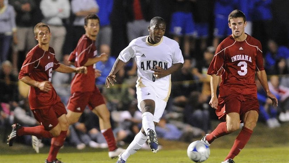Three Indiana defenders track Akron forward Nagbe Darlington as he passes the ball during the University of Akron Tournament Friday night in Akron, OH.  The Hoosiers lost 1-0 to Akron Friday night and defeated Florida International 2-1 in double overtime on Sunday.