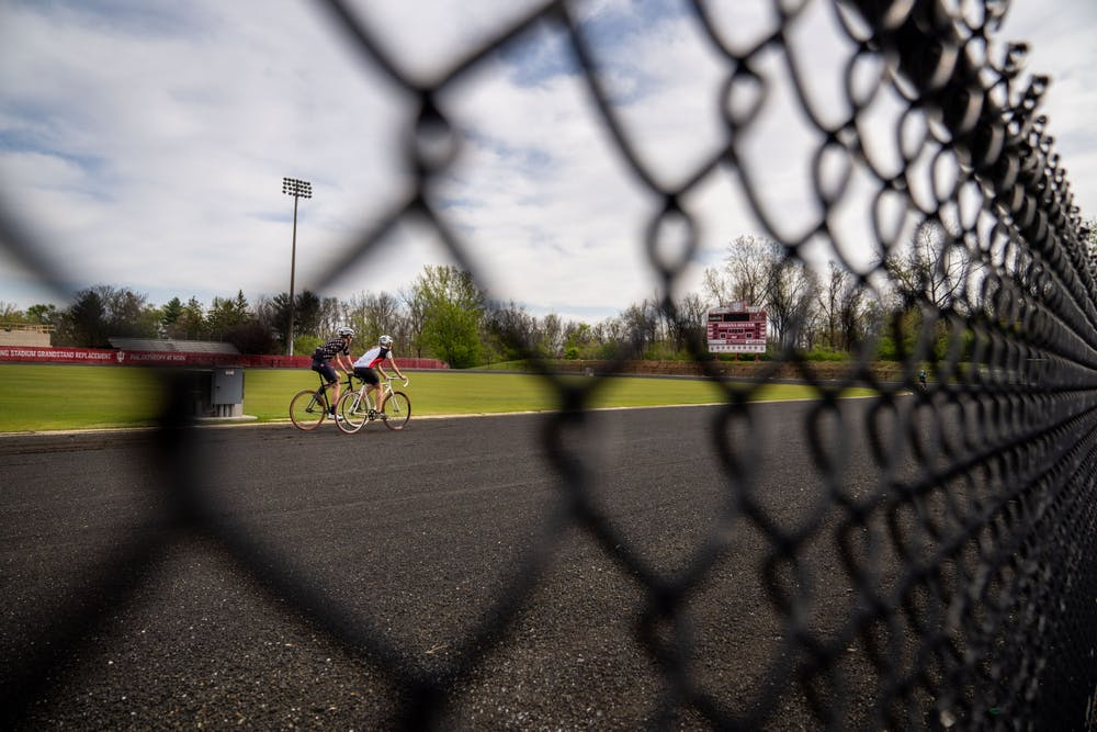 <p>Two riders ride around the track April 25 at Bill Armstrong Stadium. While the 2020 Little 500 race was canceled, riders found their own ways to celebrate the weekend.</p>