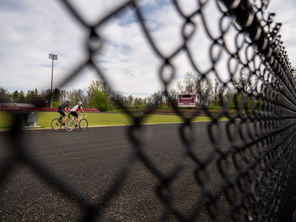 Two riders ride around the track April 25 at Bill Armstrong Stadium. While the 2020 Little 500 race was canceled, riders found their own ways to celebrate the weekend.