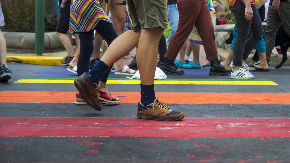A man walks along Kirkwood Avenue Aug. 31, 2019, at Bloomington Pridefest. Crosswalks along Kirkwood were painted in rainbow colors for the festival, which will be virtual in 2020.