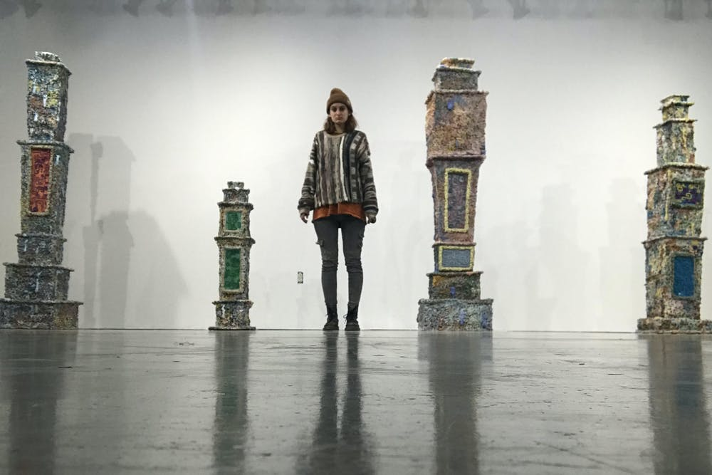 <p>Senior Persis Wade stands by her art work at the BFA thesis exhibition at the Grunwald Gallery of Art. Wade constructed tombstones using clay to honor the dead. </p>