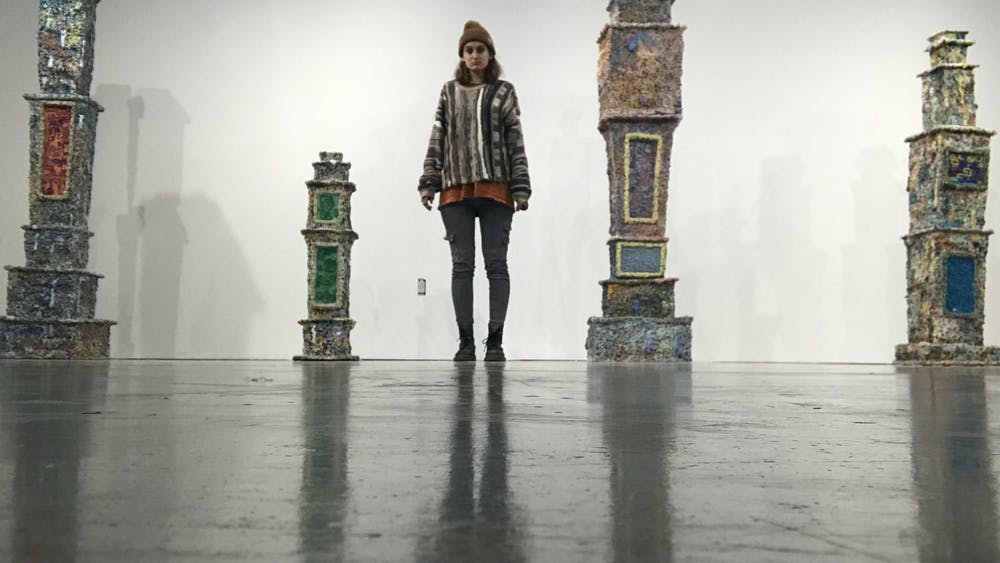 Senior Persis Wade stands by her art work at the BFA thesis exhibition at the Grunwald Gallery of Art. Wade constructed tombstones using clay to honor the dead.