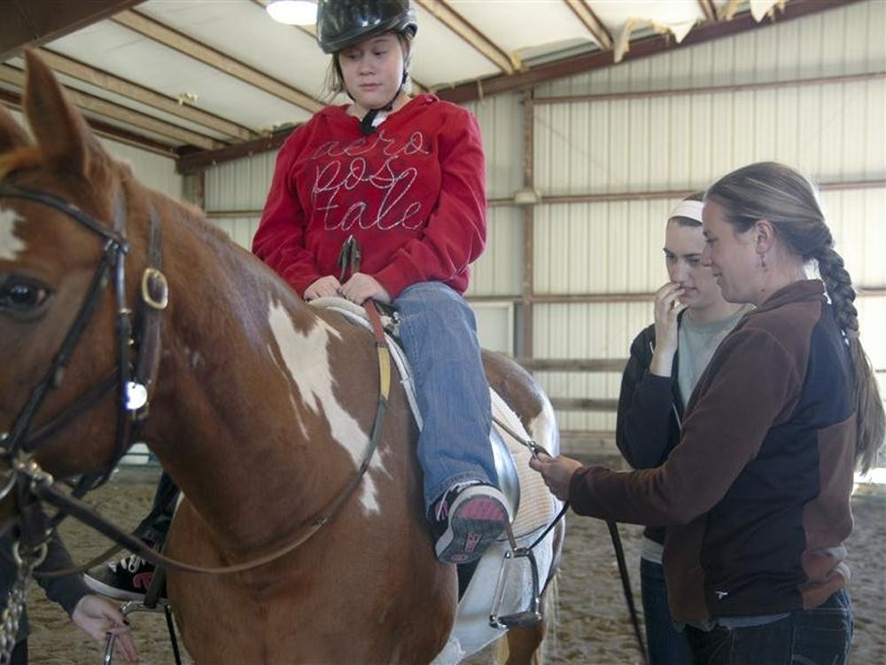 Libbie, a child with spina bifida, rides Cody, the head riding instructor Jennifer Lung's favorite horse Tuesday at Ellington Stables. Ellington Stables is home to People and Animals Learning Services (PALS) which is an Equine Assisted Program that provides therapeutic riding for children and adult's with disabilities.