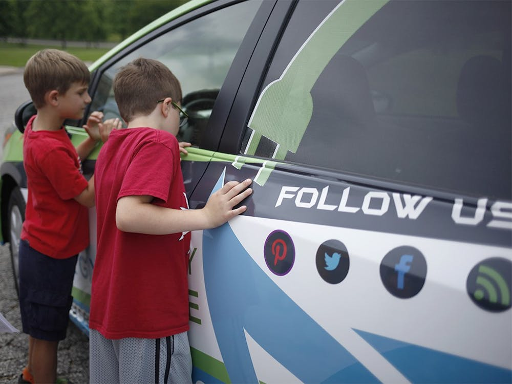 From left, second grade students Levi Schroeder and Mason Powwell look inside the EnergyMobile Wednesday at Marlin Elementary School.  The car visited three local schools throughout the day to promote sustainability to students.