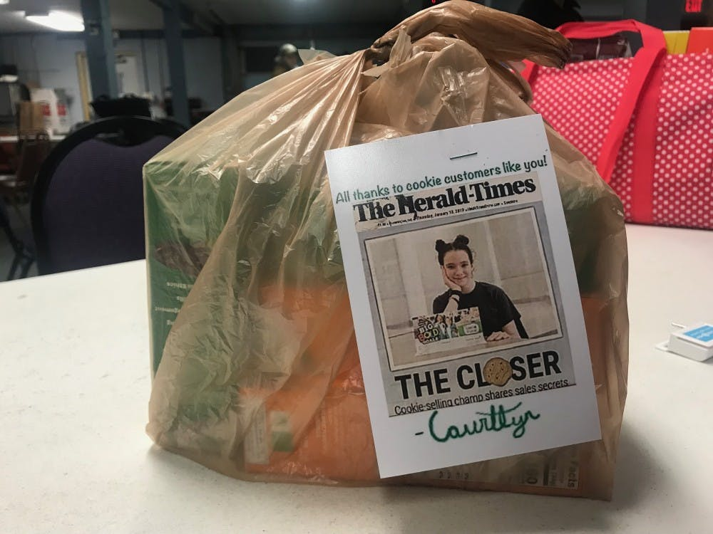 A bag of Girl Scout cookies sits on a table Feb. 19 at the Veterns of Foreign Wars post in Bloomington. Courtlyn Bales-Hall puts some boxes of preordered cookies in bags to be delivered.