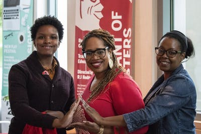 Adriann Wilson, Clarisa Isom and Shulana Kpabar make a triangle sign with their hands June 19 at their booth in the Neal-Marshall Black Cultural Center. The women are members of Delta Sigma Theta Sorority, Inc. and partnered with Half Price Books to give away free books.