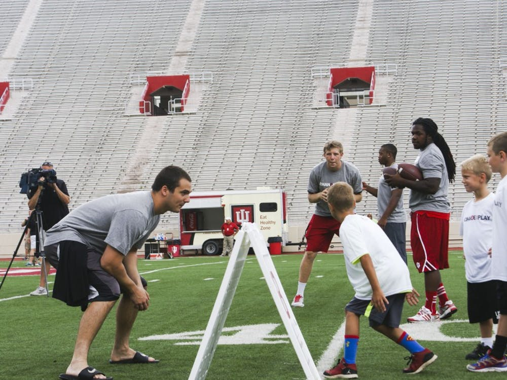IU quarterback Nate Sudfeld and defensive end Nick Carovillano play with children during the Change the Play event Tuesday in Bloomington.