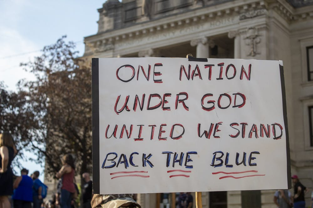 """<p>A sign reading """"one nation, under God, united we stand, back the blue"""" is held during a protest Aug. 22 at the Monroe County Courthouse. At least 200 people were in attendance. </p>"""