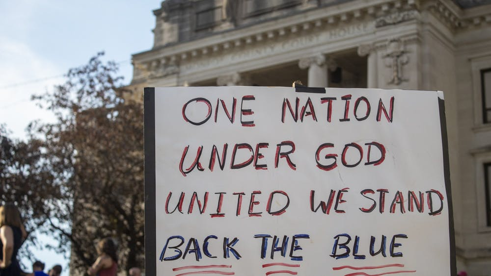 """A sign reading """"one nation, under God, united we stand, back the blue"""" is held during a protest Aug. 22 at the Monroe County Courthouse. At least 200 people were in attendance."""