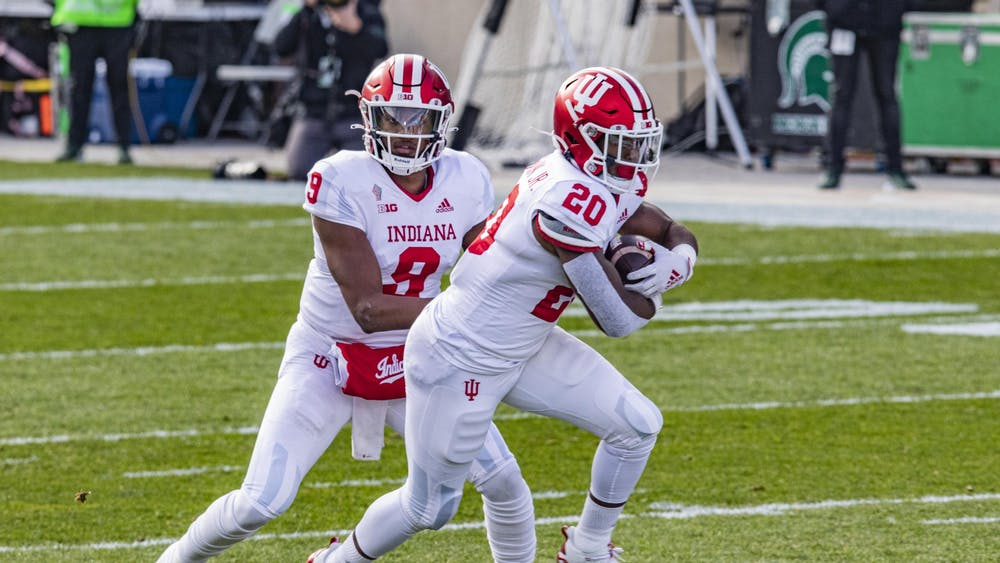 Then-sophomore quarterback Michael Penix Jr. passes the ball to then-freshman running back Tim Baldwin Jr. on Nov. 14, 2020, in Spartan Stadium in East Lansing, Michigan. Baldwin entered the NCAA transfer portal, Indiana football head coach Tom Allen said in a press conference Monday.