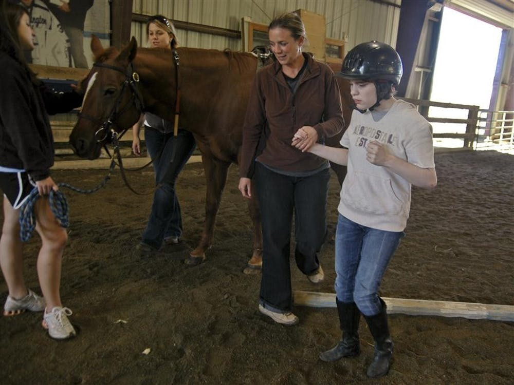 Jennifer Lung, the head riding instructor of People and Animals Learning Services, Inc. (PALS) of Bloomington, walks with Taylor, a 14-year-old with spastic cerebral palsy, and horse Patti on Oct. 5 at the PALS barn.