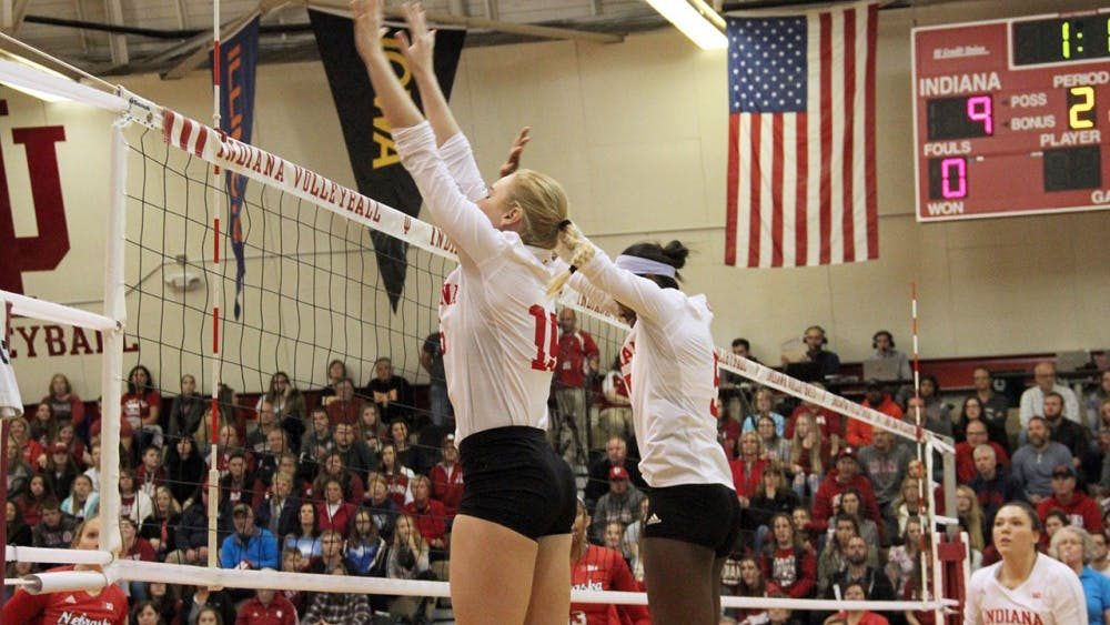 Mallory Waggoner (left) and Jazzmine McDonald block the ball as IU Volleyball competes against Nebraska on Saturday.