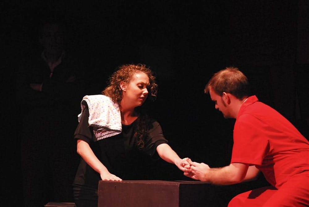 """Junior Julia Mosby and senior David Johnson perform as husband and wife Liz and Benny Saturday in """"Small Box"""" at the Buskirk-Chumley Theater. In the opera about life on death row, Benny has just broken the news that his execution date has been set."""