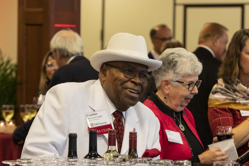 <p>IU Alumni Association life member Franklin Breckenridge smiles while ordering a drink Oct. 10 in Alumni Hall. IU alumni could drink and converse before having dinner. </p>