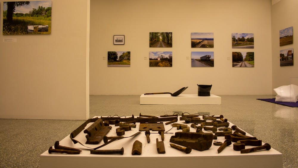 "An installation by Betsy Stirratt sits in the foreground, and photos by Richard Koenig hang in the background Tuesday at the Grunwald Gallery of Art. Koenig and Stirratt both have work being featured in Grunwald's new exhibit, ""Hoosier Lifelines: Environmental and Social Change Along the Monon, 1847-2020."""