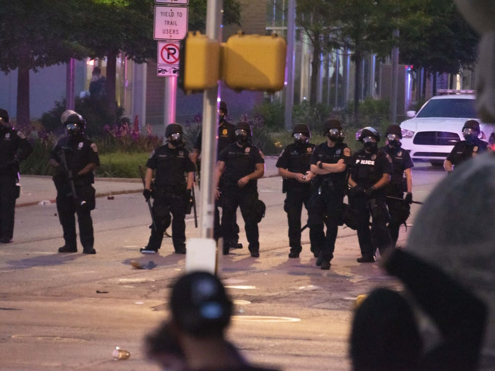 Police stand in a line at an intersection May 30 in downtown Indianapolis during a protest over the killing of George Floyd by Minneapolis police officer Derek Chauvin.