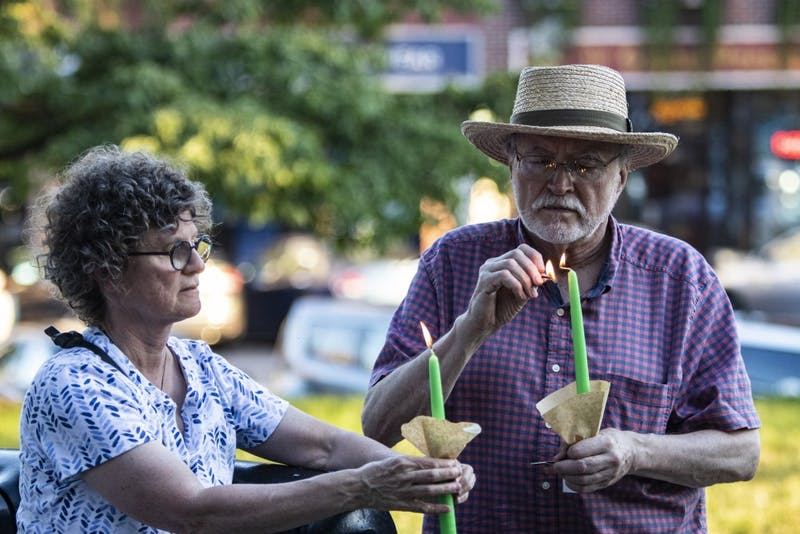 """Bloomington residents Susan Schwibz and Roy Sillings light their candles before participating in the """"Lights for Liberty"""" vigil July 12 in front of the Monroe County Courthouse. """"You can't treat people like this,"""" said Schwibz when talking about human detention centers in the United States."""