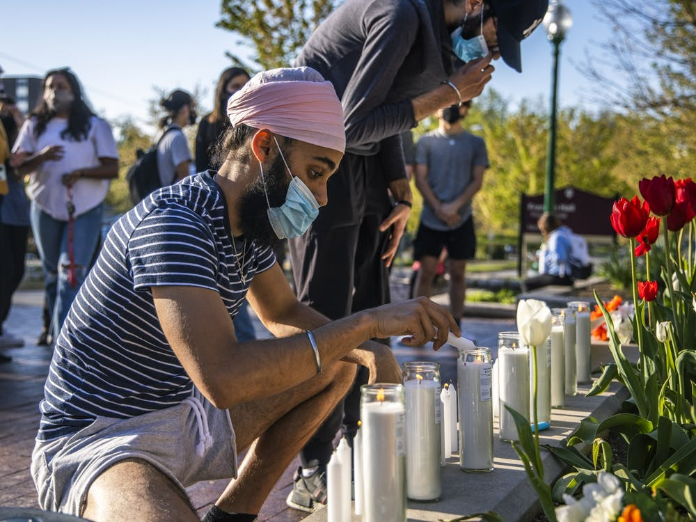 Freshman Mohkm Singh lights candles before the Sikh Student Association's vigil begins Sunday in front of the Sample Gates. A crowd of about 35 people attended the vigil.