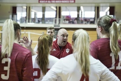 Women's volleyball head coach Steve Aird huddles the whole team after the second game at the Cream & Crimson scrimmage Aug. 18 in Assembly Hall. IU is 12-7 this season and 3-5 in Big Ten Conference play.