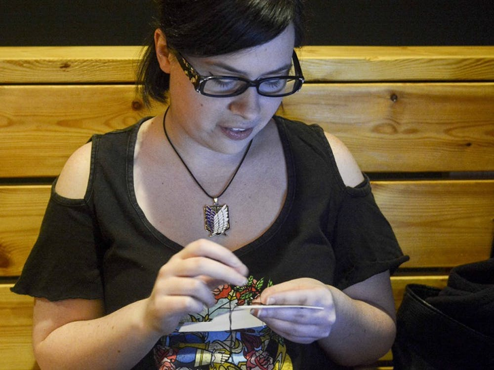 """Abby bouen makes cross stitching in the Valentine's themed """"Stitch & Bitch"""" event on Monday evening at Cardinal Spirits."""
