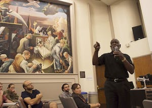 Charles Nelms, the first audience member to speak once the discussion opened up to the everyone, argues that the Benton murals, which have been split into many pieces across campus, need to be brought back together so the message of the entire piece of art is clear. The Benton mural, seen behind Nelms, portrays a hooded Klan member and has caused much controversy since it was created in 1941.