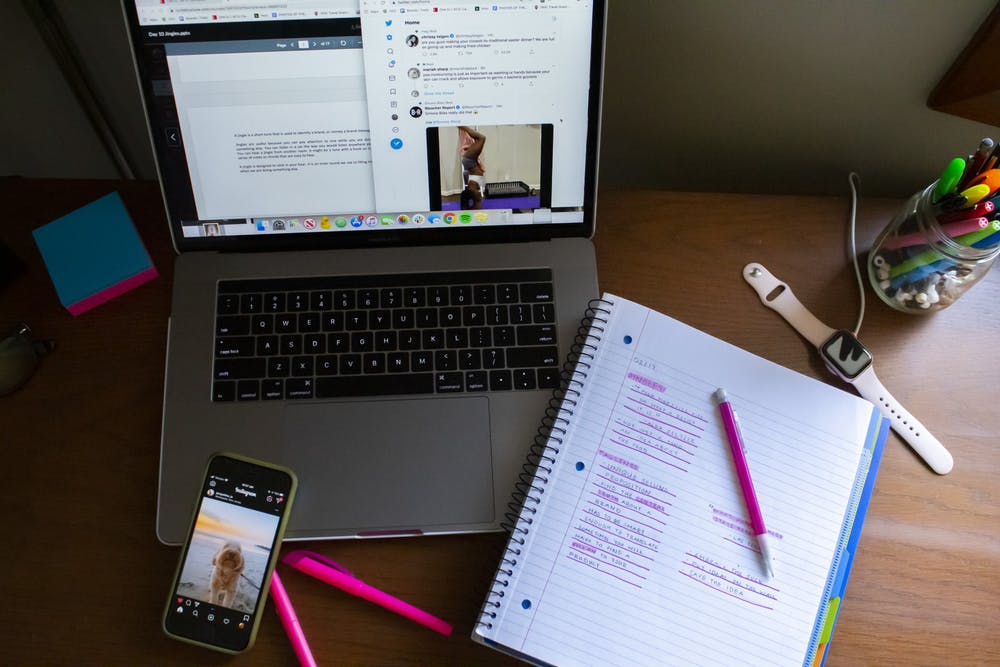 <p>Notes, a laptop and a phone displaying social media posts fill a student's desk.</p>