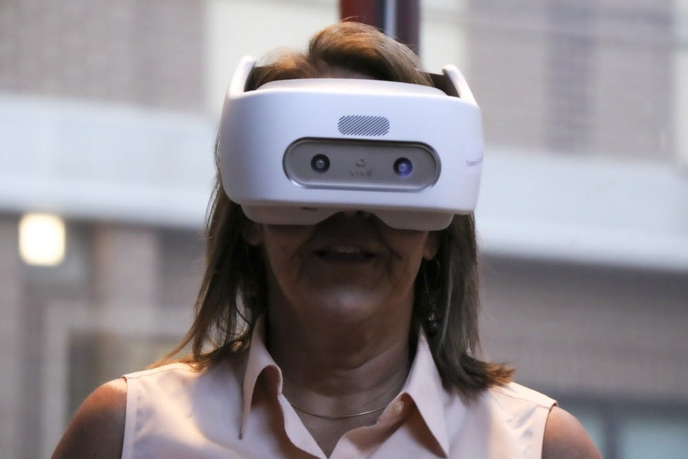 <p>Kari Costello tests a virtual reality mask at RegattaVR's open house Oct. 1 in downtown Bloomington. RegattaVR offers virtual reality programs for businesses to train employees to handle difficult situations in the workplace, such as sexual harassment.</p>