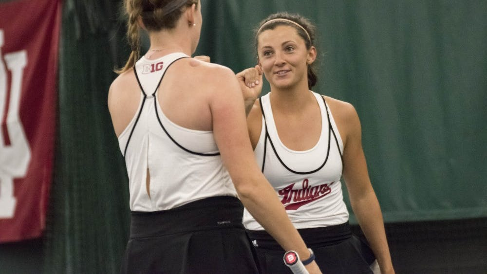 Freshman Michelle McKamey, far, and sophomore Caitlin Bernard, near, celebrate winning a point during their doubles match against Penn State. The Hoosiers need to stay within the top 10 this weekend to qualify for the Big Ten Tournament.