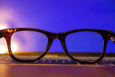 A photo illustration shows a pair of blue light glasses resting in front of a laptop screen.